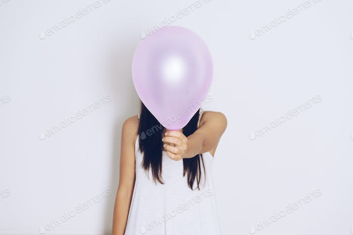 Woman holds balloons in a white background