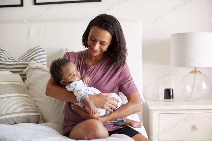 Madre de raza mixta milenaria sentada en su cama sosteniendo a su Bebé de tres meses en sus brazos