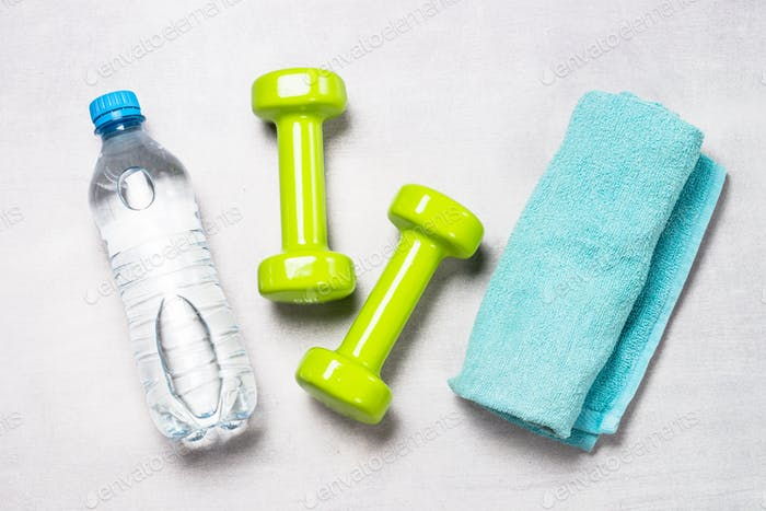 Dumbbells, water and towel on light background top view.