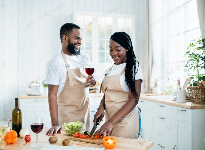 Aperitif Drink. Happy Black Spouses Drinking Wine While Cooking Food In Kitchen