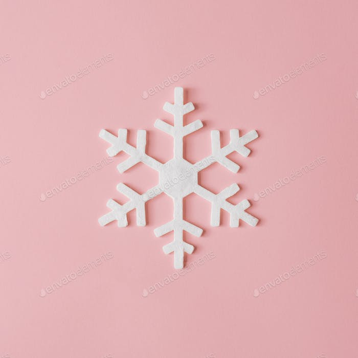 Christmas snowflake decoration with pink background. Minimal concept.