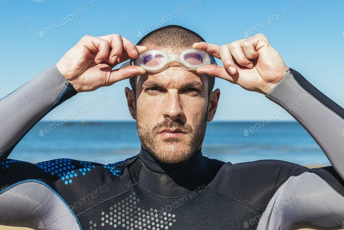 handsome swimmer putting on goggles