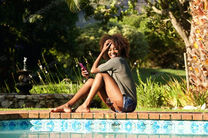 Smiling young woman with cellphone sitting by pool