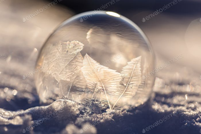 Soap bubble in the snow in winter. Ice patterns on the surface