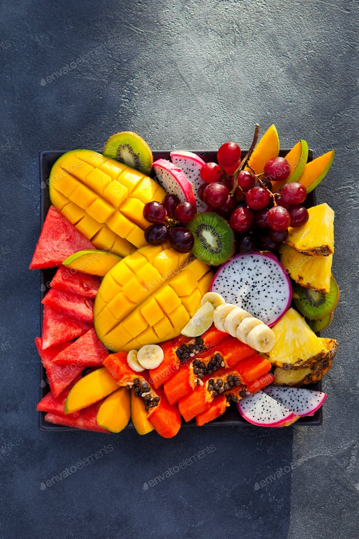 Tropical Fruits Assortment on a Plate. Slate Background. Copy Space. Top View.