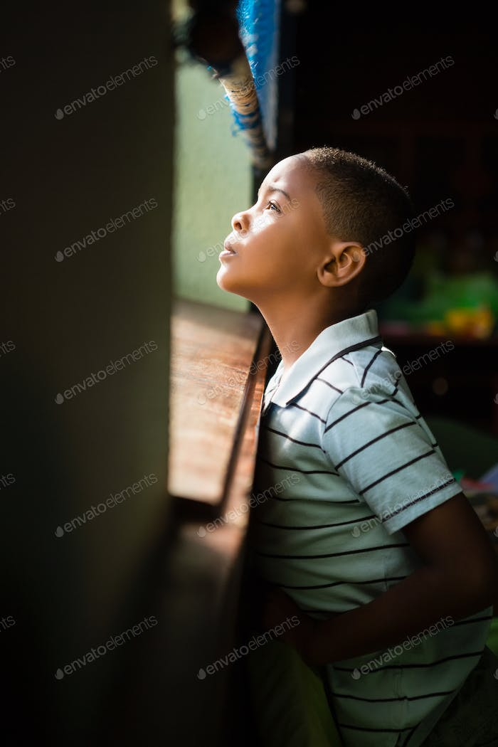 Thoughtful boy looking through window