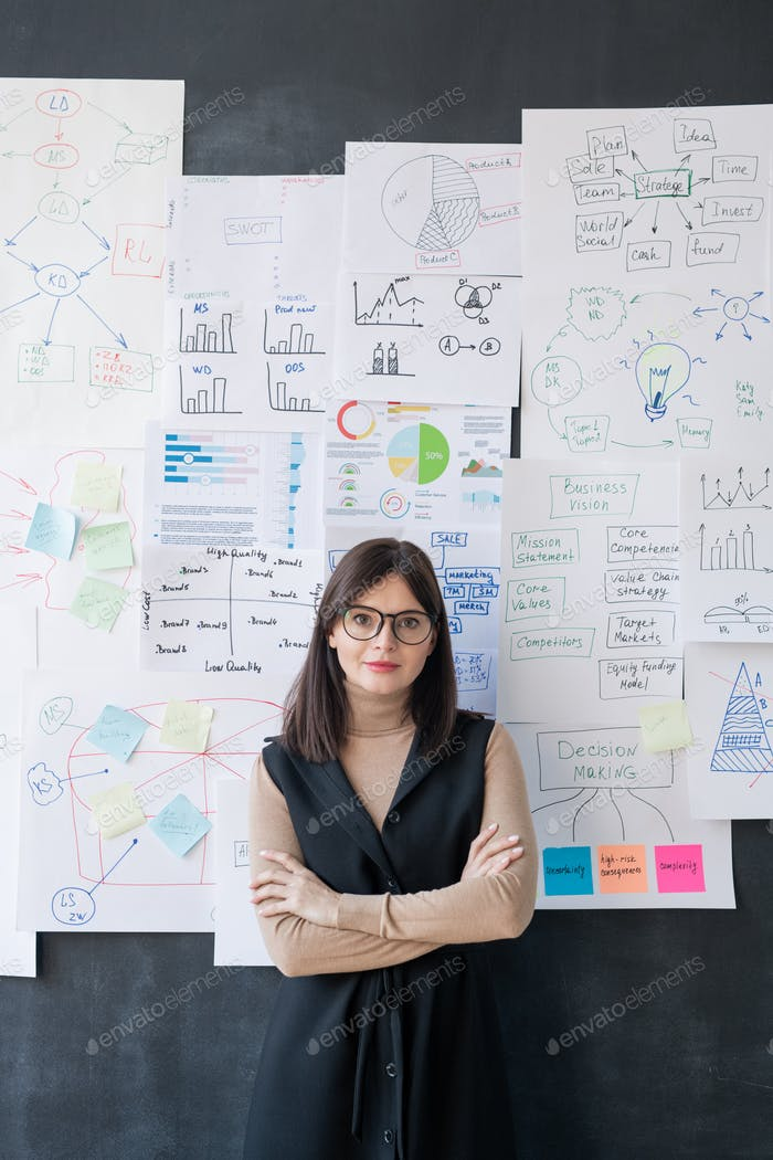 Young economist standing by blackboard with flow charts and diagrams on papers
