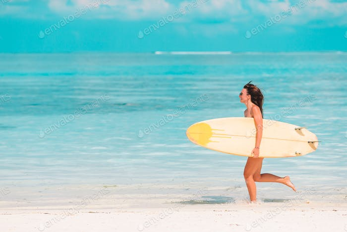 Beautiful surfer woman ready to surfing in turquoise sea, on stand up paddle board at exotic