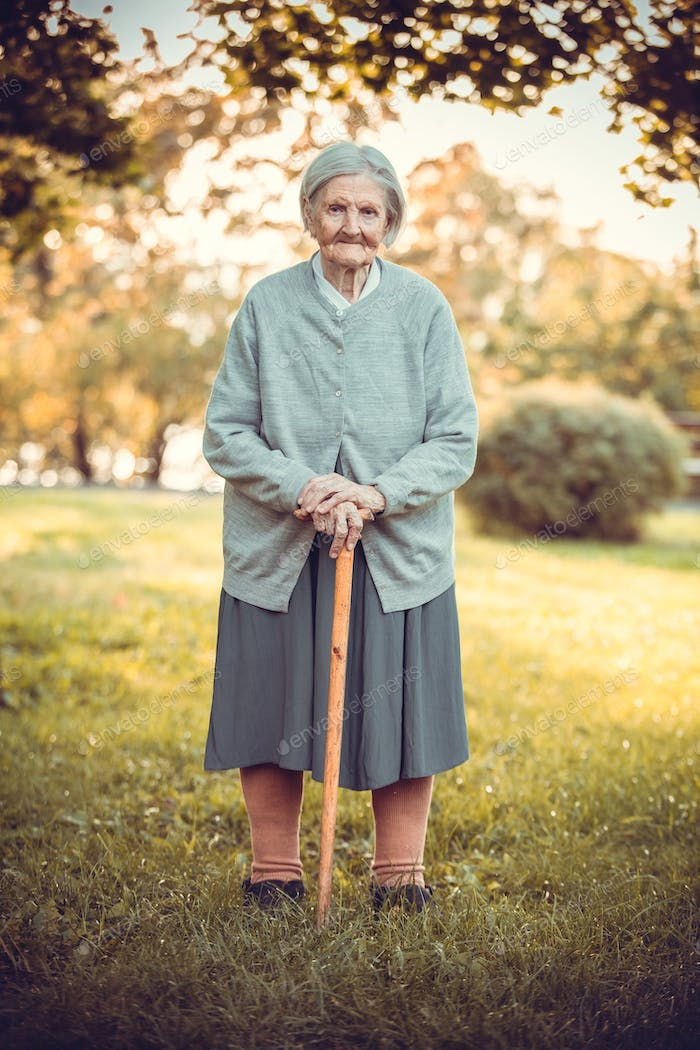 Senior woman with walking stick in autumn park