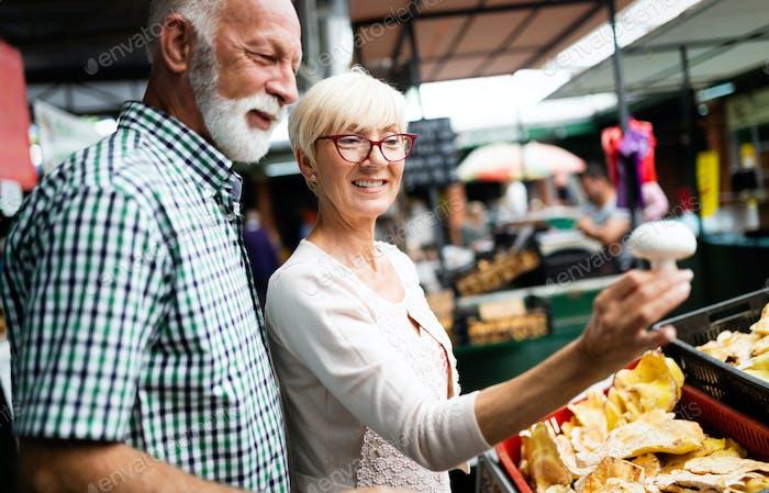 Älteres Familienpaar wählen Bio-Lebensmittel Obst und Gemüse auf dem Markt während der wöchentlichen Einkäufe