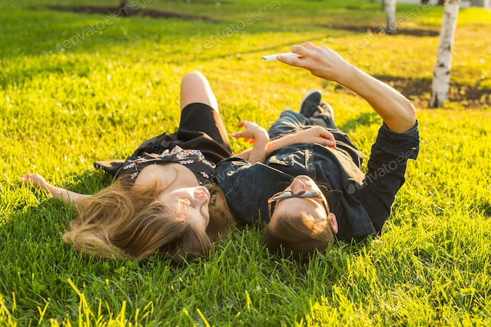 Spring outdoor portrait of young happy couple lying on the grass