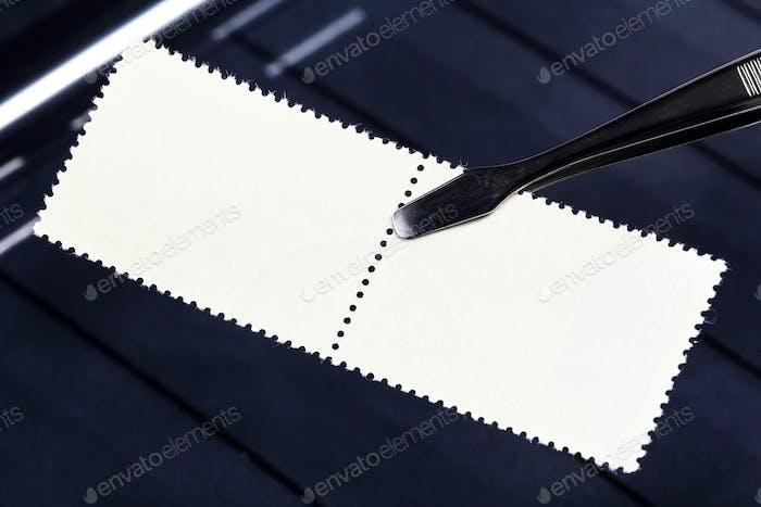 Zange hält Briefmarken mit minziger Rückseite