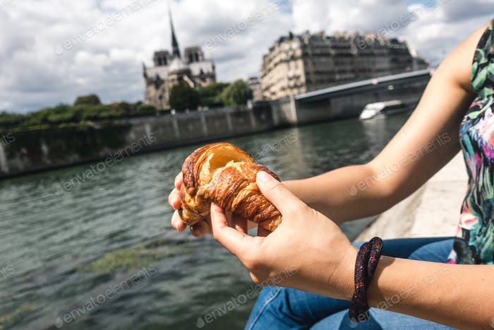 Girl eating croissant in Paris