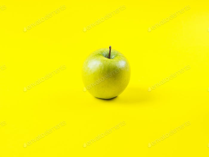 Shiny green apple on bold yellow background