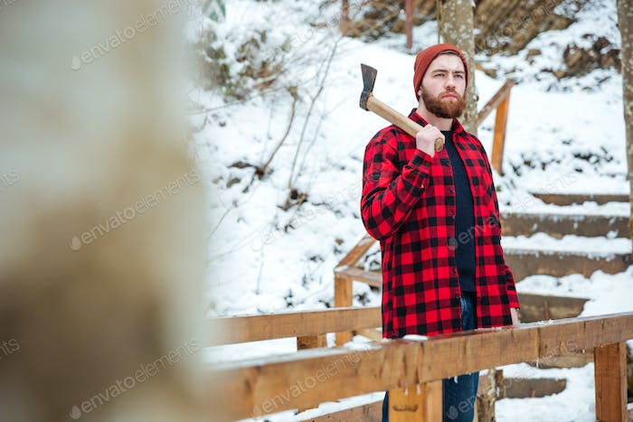 Bearded man holding axe and thinking in winter forest