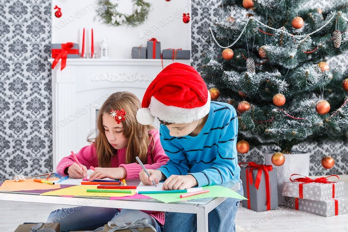 Cute children writing letter to santa, wait for christmas