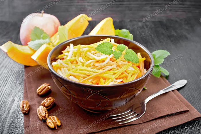 Salad of pumpkin and apple in bowl on dark board