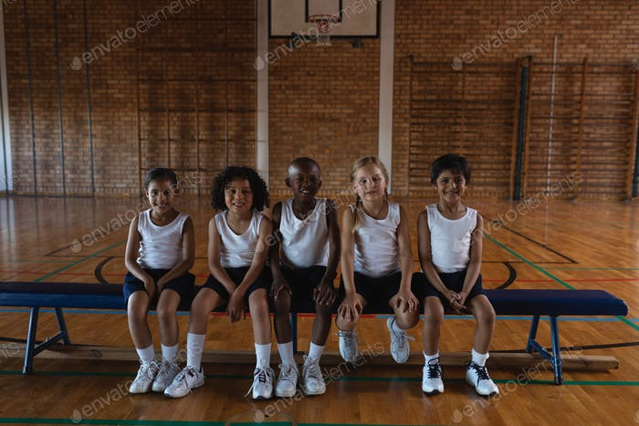 Front view of schoolkids looking at camera while sitting on bench at basketball court in school