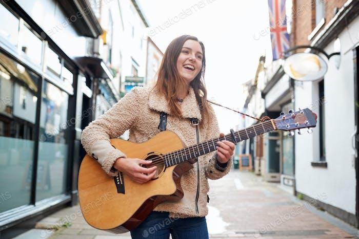 weiblich musiker busking spielen akustische gitarre im freien in street