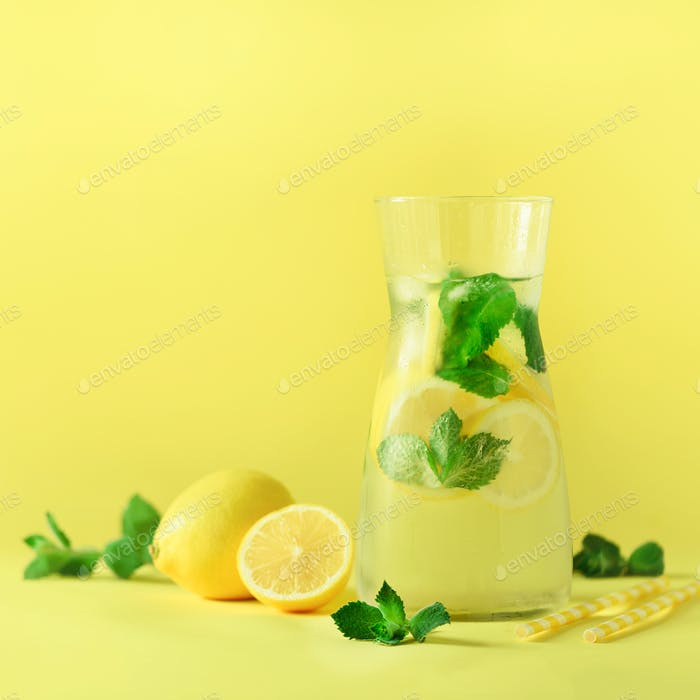 Fresh summer fruits water or lemonade with mint, ice, lemon on yellow background. Square crop. Copy