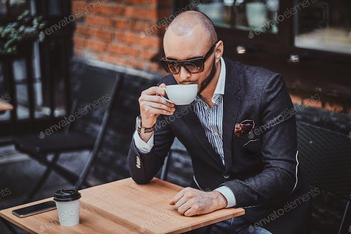 Привлекательный ухоженный человек наслаждается кофе