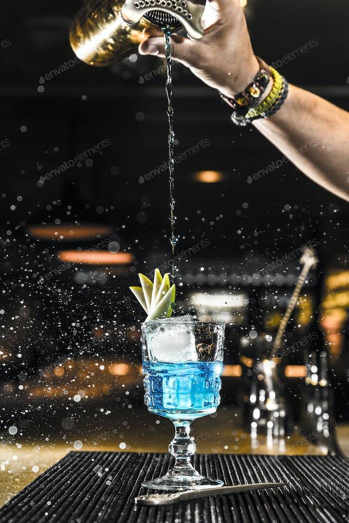Barman gießt einen Cocktail in ein Glas