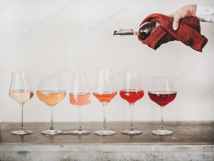Rose wine shades and womans hand pouring wine to glass