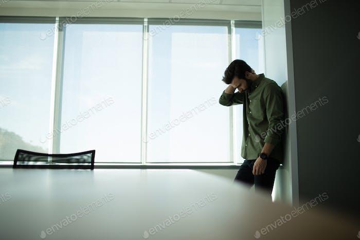 Depressed businessman standing by window