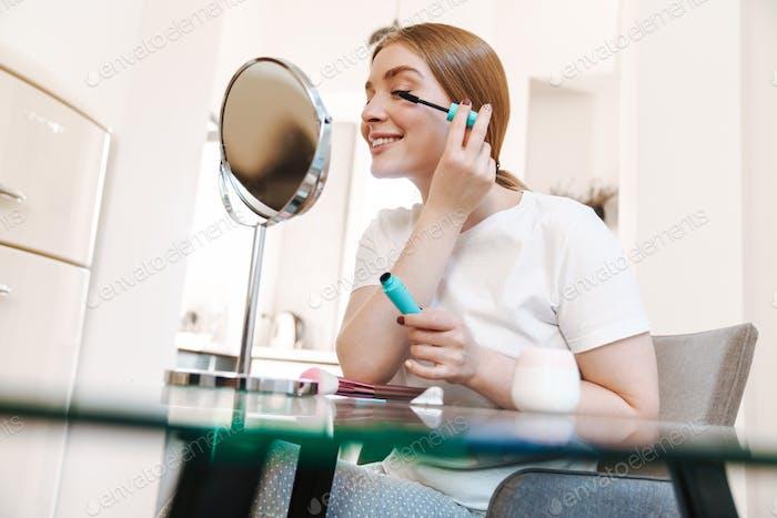 Konzentrierte Mädchen drinnen zu Hause mit Spiegel auftragen Make-up