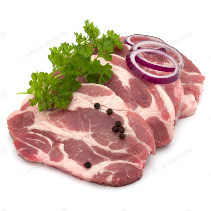 Raw pork neck chop meat with parsley herb leaves, peppercorn spices and onion slices garnish
