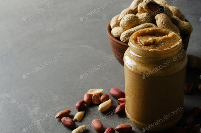 Low angle view at glass mason jar with peanut butter on stone table. Healthy eating concept