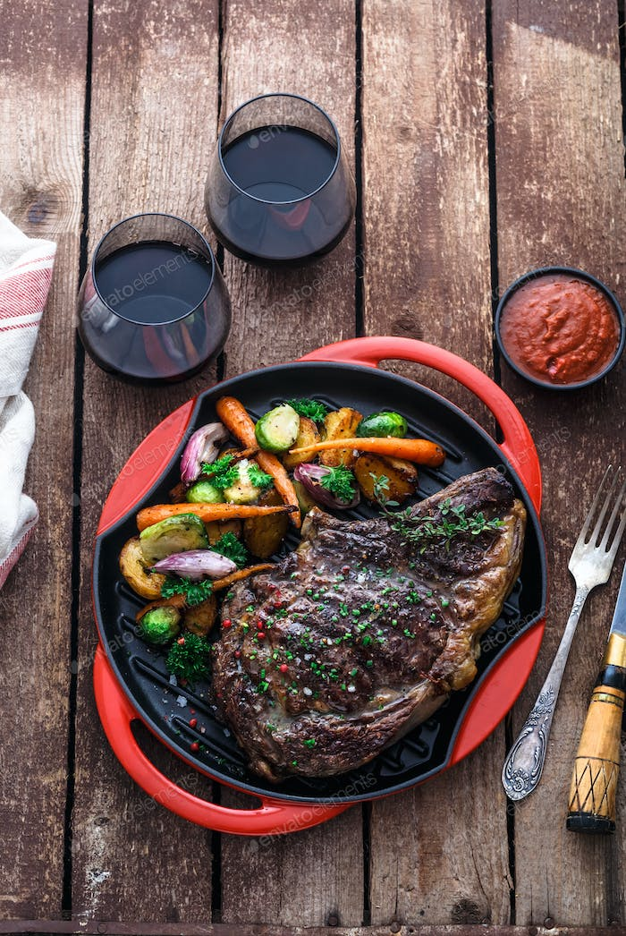 Grilled Beef Steak on grill iron pan on wooden background