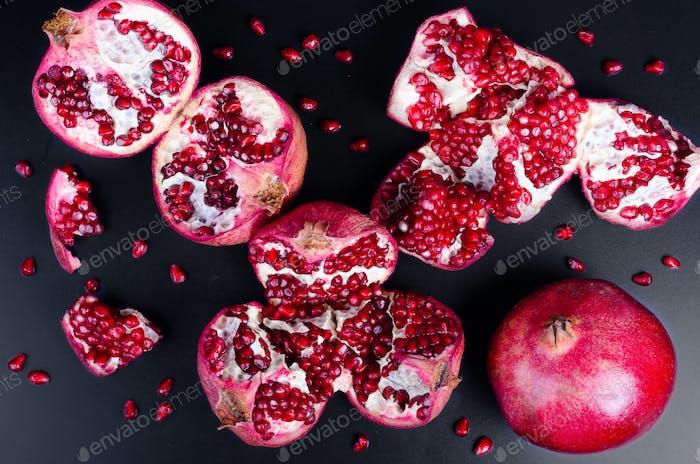 Gebrochener Granatapfel und Körner auf schwarzem Hintergrund. Kopierbereich