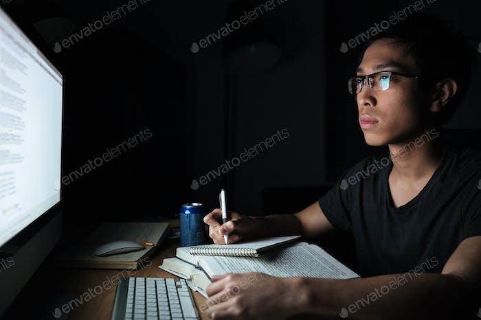 Man schreibt im Notizblock und mit Computer