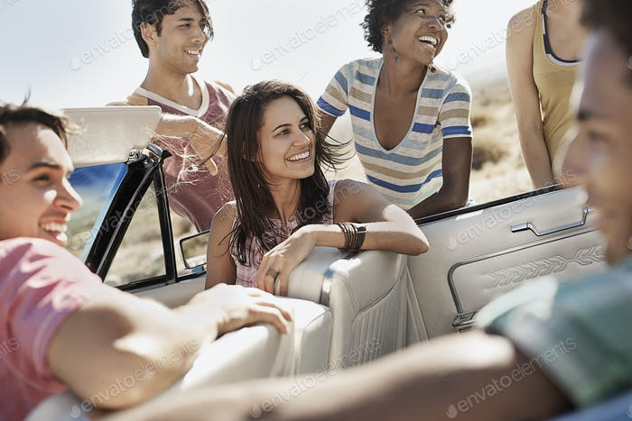 A group of friends in a pale blue convertible on the open road