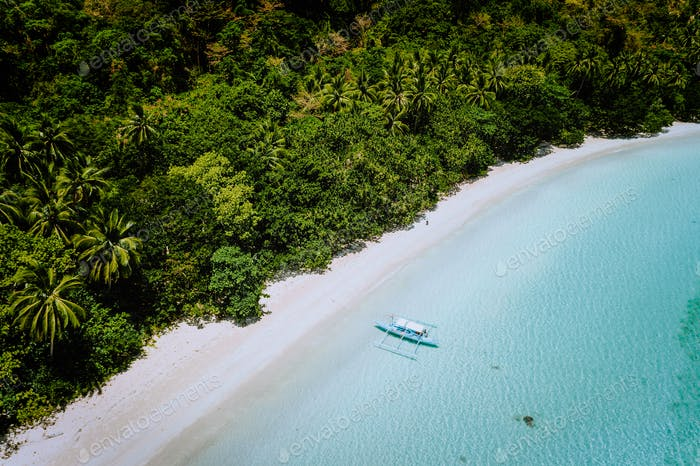 Aerial drone view of a beautiful secluded deserted tropical beach. Lonely boat in turquoise lagoon