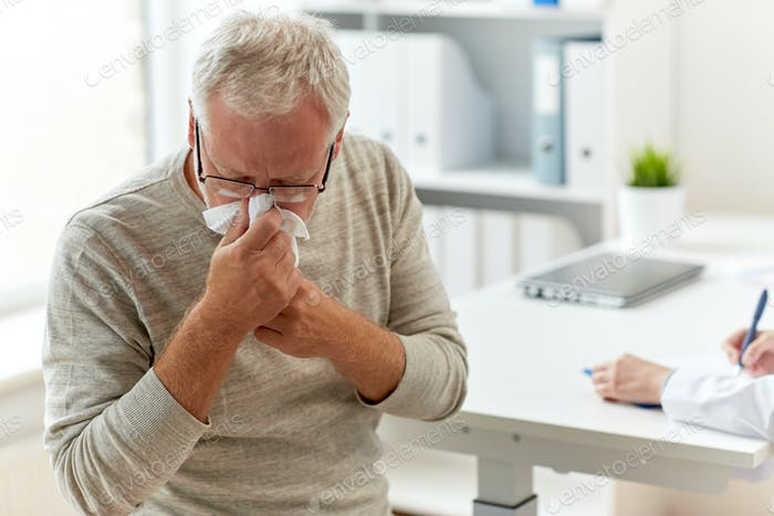 senior man blowing nose with napkin at hospital