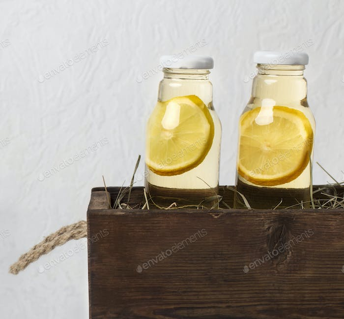 Citrus fruits and herbs infused water for detox diet in wooden box