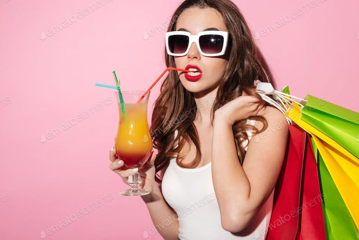 Girl in sunglasses holding colorful shopping bags and drinking cocktail