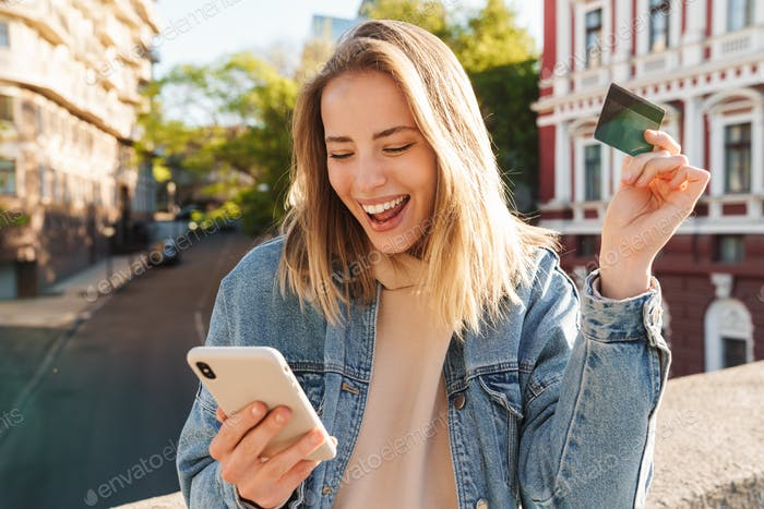 Cheerful young blonde girl shopping online with mobile phone