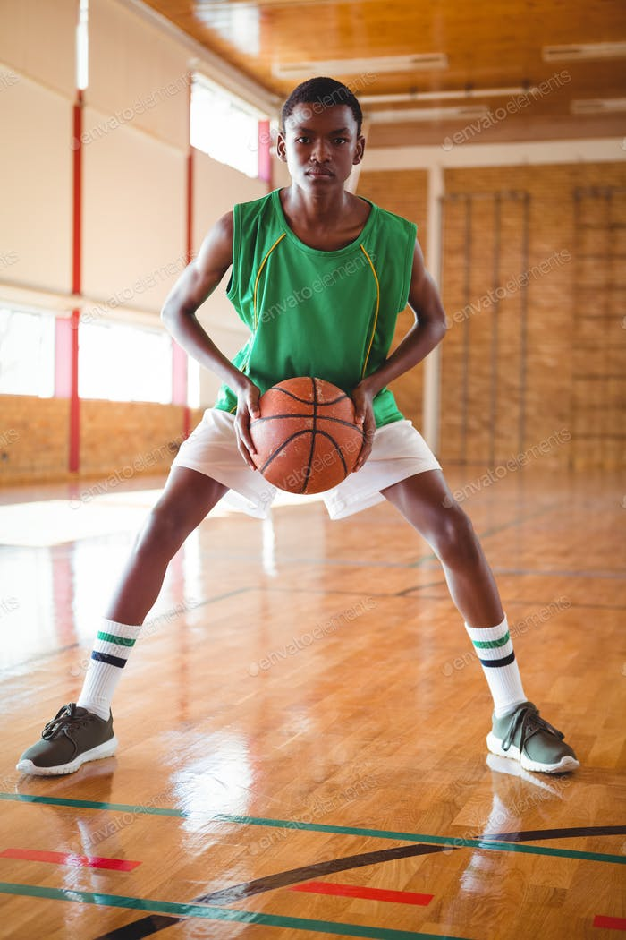 Portrait of teenage basketball player in court