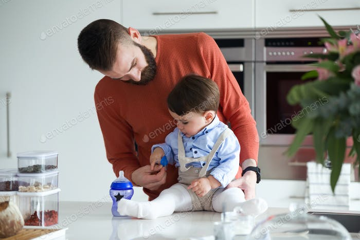 Handsome young father with his baby playing in the kitchen at home.