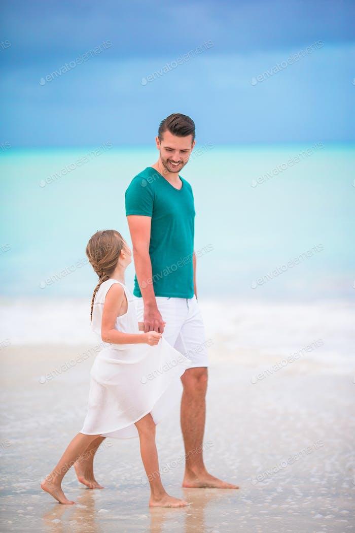 Glücklicher Vater und seine entzückende kleine Tochter am tropischen Strand zu Fuß zusammen