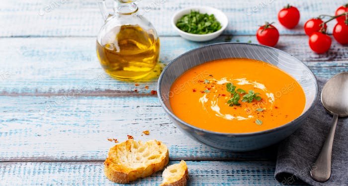 Pumpkin and carrot cream soup in a bowl. Blue wooden background. Copy space.