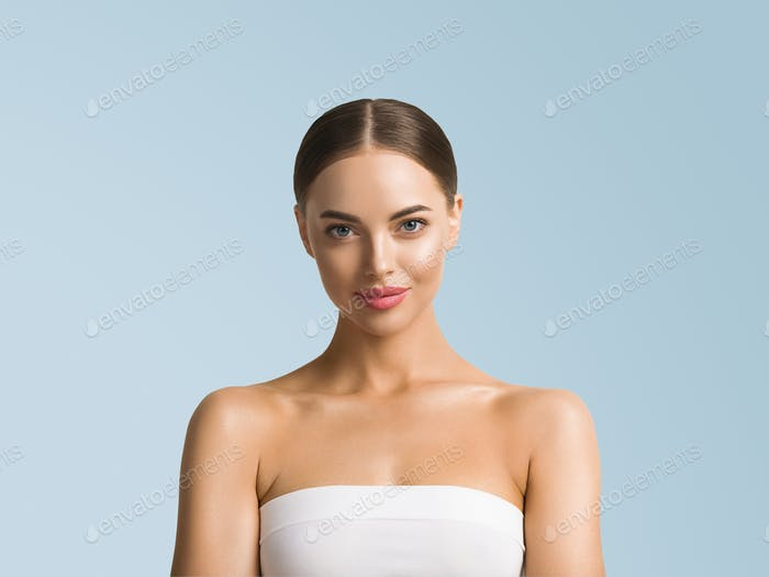 Clean skin beauty woman face healthy skin natural make up tanned female over blue background
