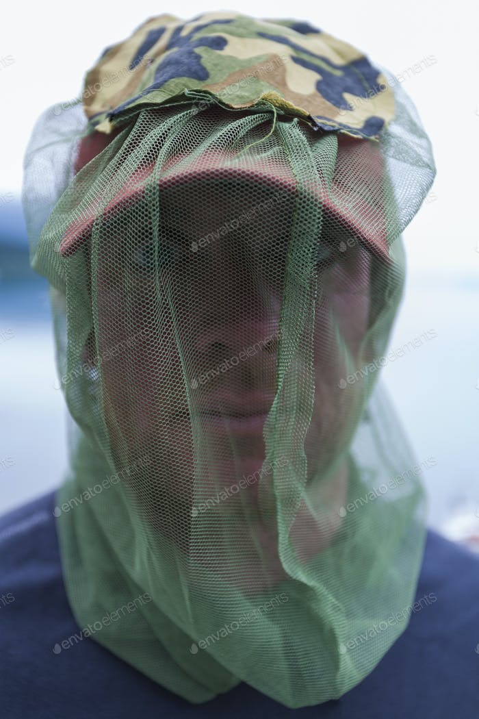 Close up of man wearing protective mosquito netting