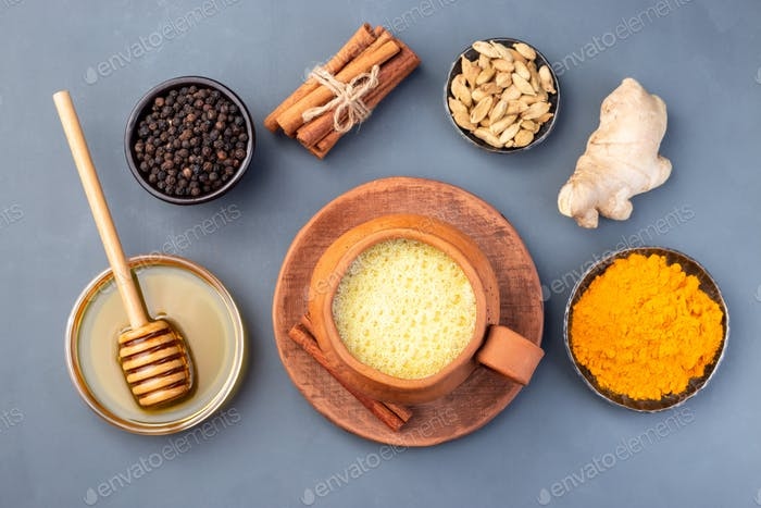 Yellow moon milk with turmeric in clay cup, ingredients on background, horizontal, top view