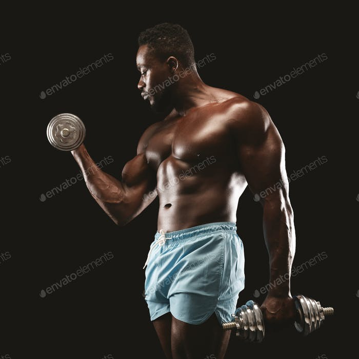 Portrait of black bodybuilder doing single arm dumbbell curl