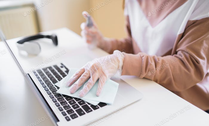 Unrecognizable young student with gloves at the table, disinfecting laptop