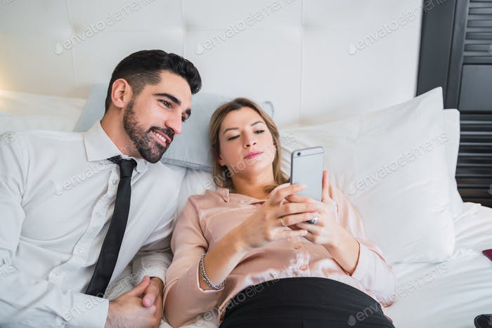 Business people lying on bed and using mobile phone.